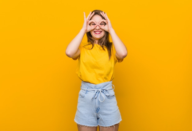 Young woman teenager wearing a yellow shirt showing okay sign over eyes