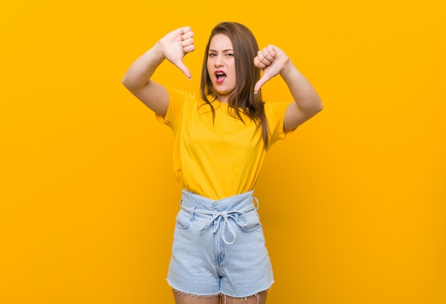 Young woman teenager wearing a yellow shirt showing thumb down and expressing dislike.