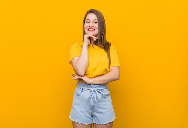 Young woman teenager wearing a yellow shirt smiling happy and confident, touching chin with hand.
