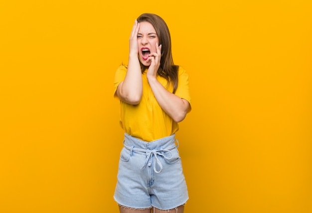 Young woman teenager wearing a yellow shirt whining and crying disconsolately