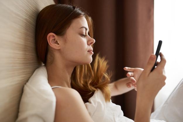 Молодая женщина-подросток с телефоном лежит в постели и оконные шторы на заднем плане