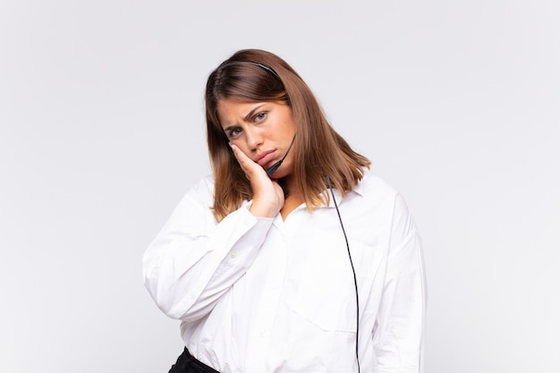 若い女性のテレマーケティング担当者は、手で顔を持って、退屈で、退屈で退屈な仕事をした後、退屈、欲求不満、眠気を感じます