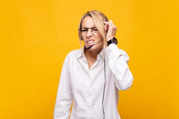 혼란스럽고 의아해하는 젊은 여성 텔레마케터는 당신이 미쳤거나 미쳤거나 정신이 나갔음을 보여줍니다.