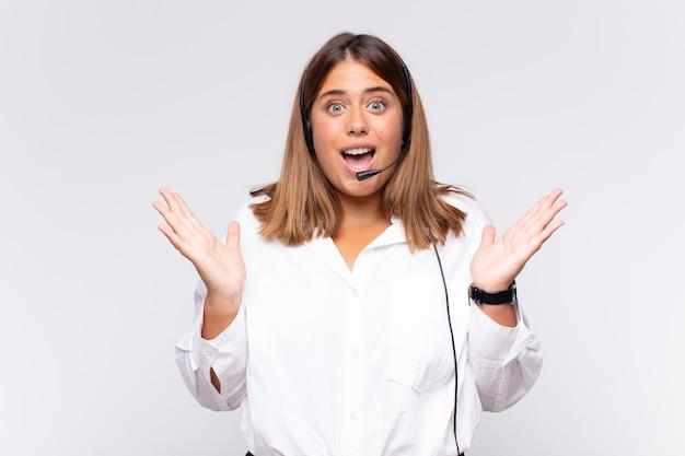 Молодая женщина-телемаркетолог чувствует себя счастливой, взволнованной, удивленной или шокированной, улыбается и удивляется чему-то невероятному