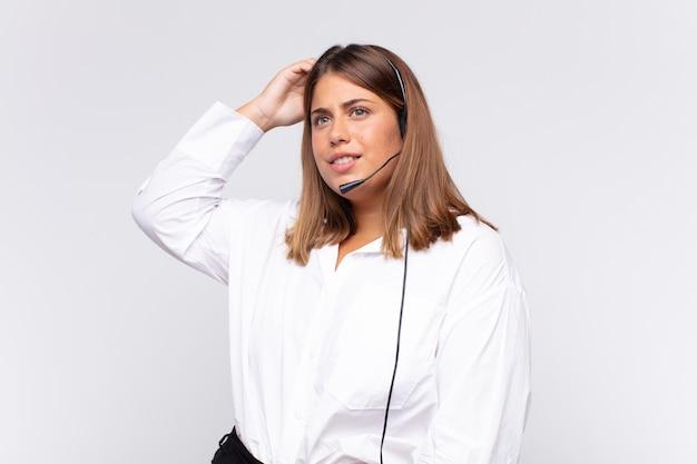 若い女性のテレマーケティング業者は、戸惑い、混乱し、頭をかいて、横を向いていると感じています