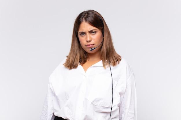 젊은 여성 텔레마케터는 슬프거나 화가 나거나 분노하고 부정적인 태도로 옆을 바라보고 의견이 일치하지 않는 인상을 찌푸립니다.