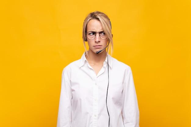 Молодая женщина-телемаркетер грустит, расстроена или злится, смотрит в сторону с негативным отношением и хмурится в знак несогласия.