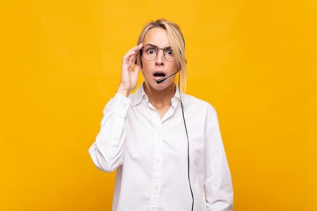 Молодая женщина-телемаркетер выглядит удивленной, с открытым ртом, шокированной, осознающей новую мысль, идею или концепцию