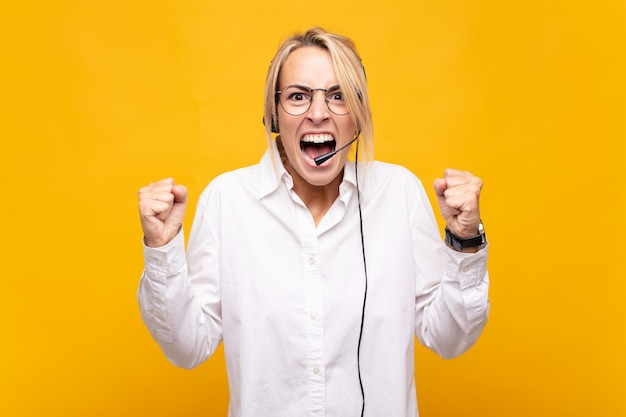 怒りの表情や成功を祝って握りこぶしで積極的に叫ぶ若い女性のテレマーケティング
