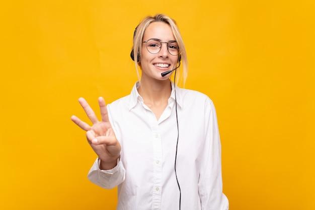 Молодая женщина-телемаркетер улыбается и выглядит дружелюбно, показывает номер три или треть рукой вперед, отсчитывая