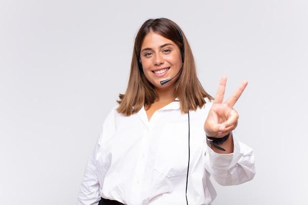 Молодая женщина-телемаркетер улыбается и выглядит счастливой, беззаботной и позитивной, жестикулируя победу или мир одной рукой