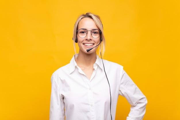 Молодая женщина-телемаркетер счастливо улыбается, положив руку на бедро и уверенно