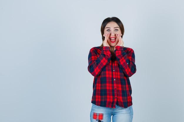 Giovane donna che dice il segreto tenendo le mani vicino alla bocca in camicia a quadri, jeans e sembra eccitata. vista frontale.