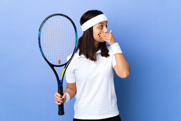 Young woman tennis player over isolated background covering mouth and looking to the side