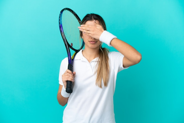 Young woman tennis player isolated on blue background covering eyes by hands. do not want to see something