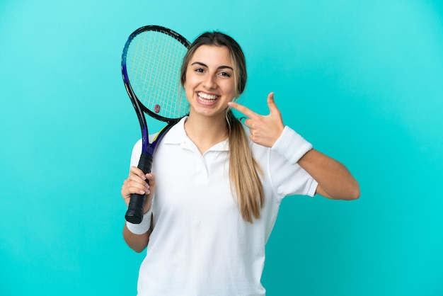 Young woman tennis player isolated on blue background giving a thumbs up gesture