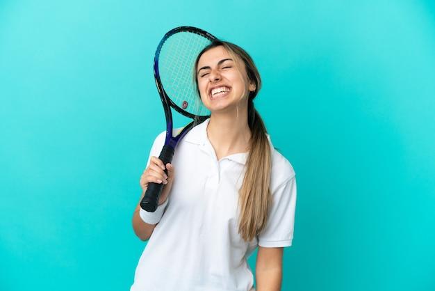 在蓝色背景笑隔绝的少妇网球员