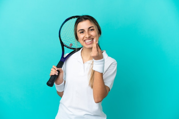 Young woman tennis player isolated on blue background making money gesture