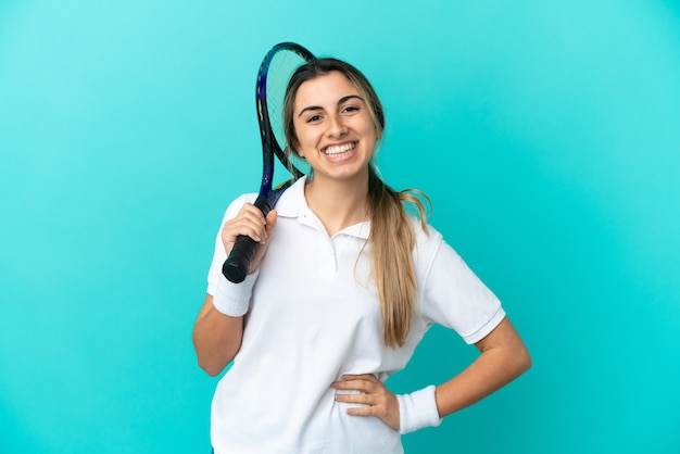 Young woman tennis player isolated on blue background posing with arms at hip and smiling