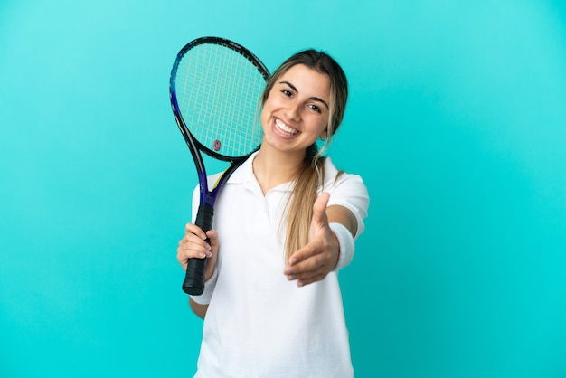 Young woman tennis player isolated on blue background shaking hands for closing a good deal