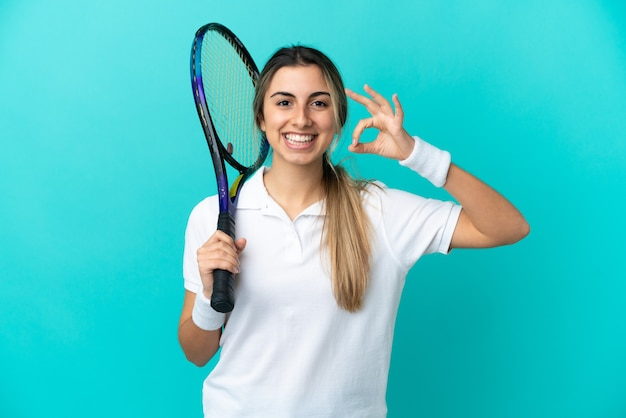 Young woman tennis player isolated on blue background showing ok sign with fingers