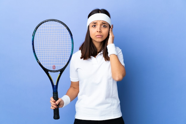 Young woman tennis player over isolated frustrated and covering ears