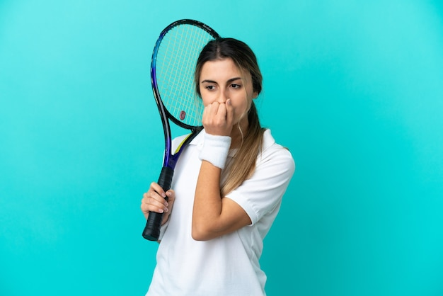파란색 배경에 의심을 품고 격리된 젊은 여성 테니스 선수