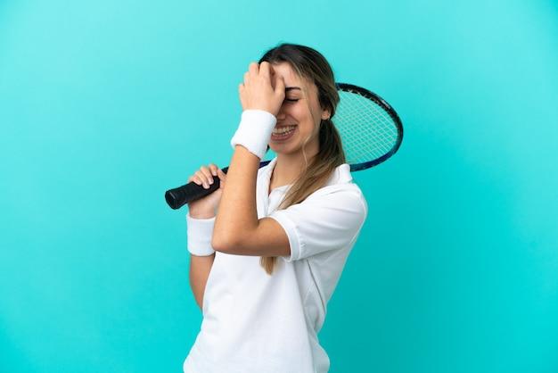 파란색 배경 웃음에 고립 된 젊은 여자 테니스 선수
