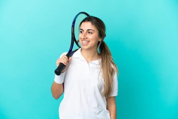 측면을 찾고 파란색 배경에 고립 된 젊은 여자 테니스 선수