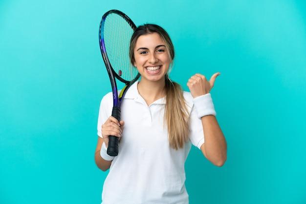 제품을 제시하는 측면을 가리키는 파란색 배경에 고립 된 젊은 여자 테니스 선수
