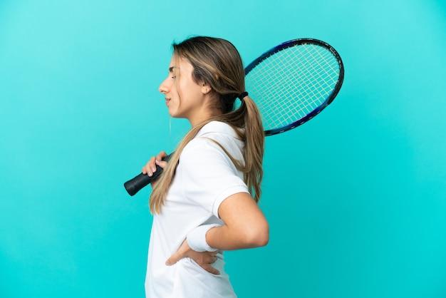 努力したために腰痛に苦しんでいる青い背景に孤立した若い女性テニスプレーヤー