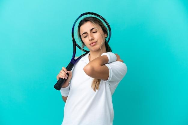努力したために肩の痛みに苦しんでいる青い背景に孤立した若い女性テニスプレーヤー