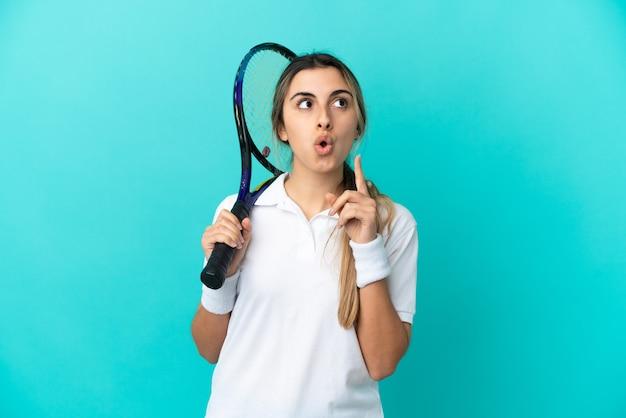 파란색 배경에 고립 된 젊은 여자 테니스 선수는 손가락을 가리키는 아이디어를 생각