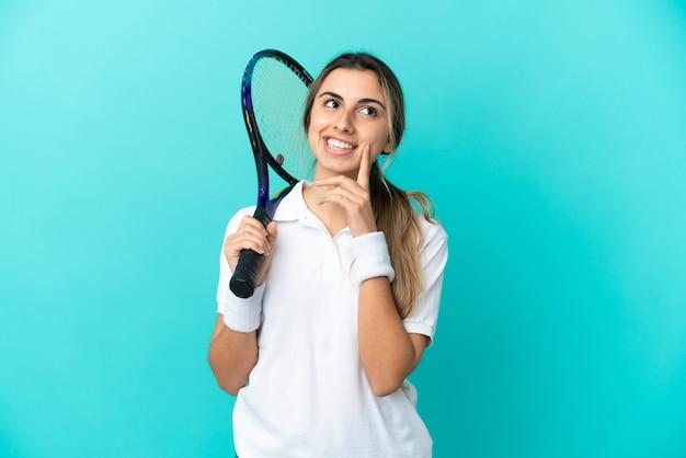 파란색 배경에 고립 된 젊은 여성 테니스 선수는 올려다 보면서 아이디어를 생각