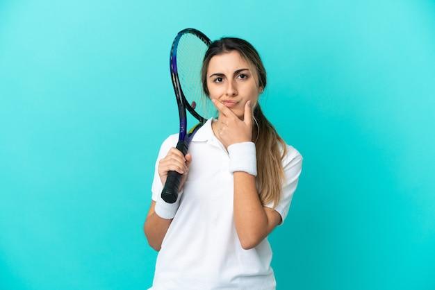 파란색 배경 생각에 고립 된 젊은 여자 테니스 선수