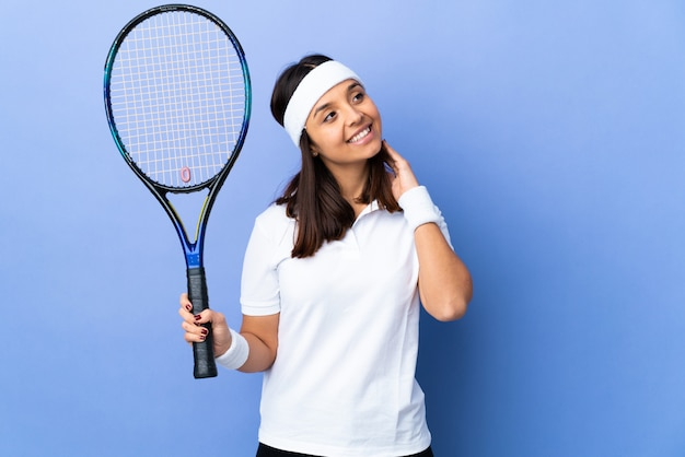 Young woman tennis player over isolated thinking an idea