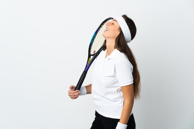 Young woman tennis player over isolated white background laughing in lateral position