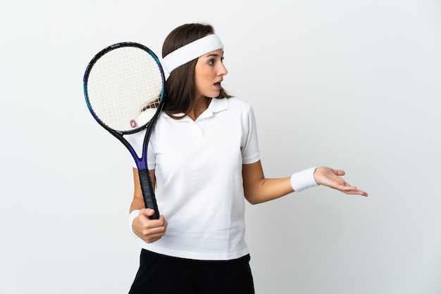 Young woman tennis player over isolated white background with surprise expression while looking side