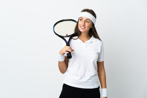 Young woman tennis player over isolated white looking to the side and smiling