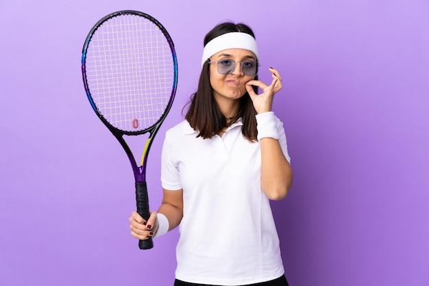 沈黙のジェスチャーの兆候を示す孤立した背景上の若い女性テニスプレーヤー Premium写真