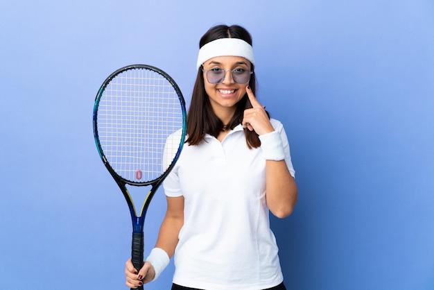 Теннисистка молодой женщины над изолированной стеной усмехаясь с счастливым и приятным выражением