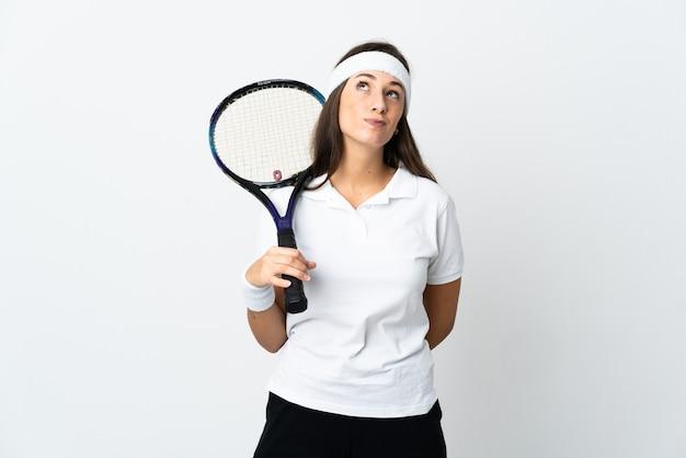 격리 된 흰색 배경 위에 젊은 여자 테니스 선수와 찾고