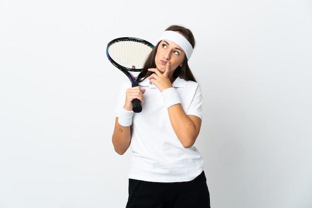 격리된 흰색 배경 위에 있는 젊은 여성 테니스 선수는 올려다보는 동안 의심을 품고 있습니다.