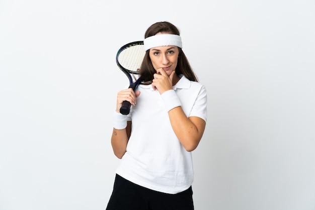 격리 된 흰색 배경 생각 위에 젊은 여자 테니스 선수