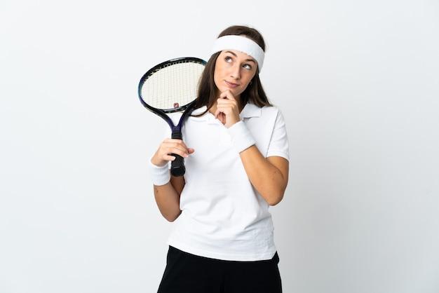 Молодая женщина-теннисистка над изолированной белой стеной и глядя вверх