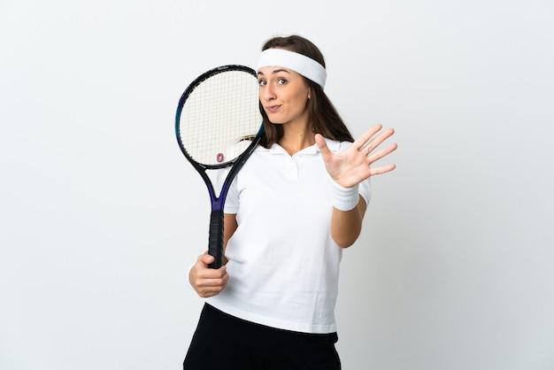 손가락으로 5 세 격리 된 흰 벽 위에 젊은 여자 테니스 선수