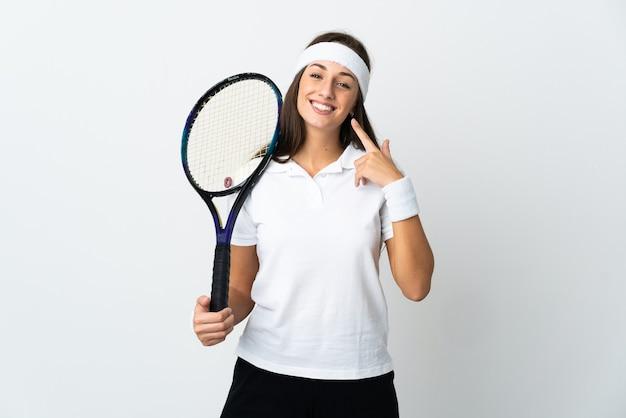 Молодая женщина-теннисистка над изолированной белой стеной, жестом показывающая палец вверх