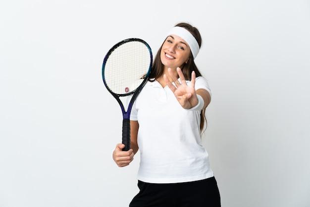 Молодая женщина-теннисистка над изолированной белой стеной счастлива и считает четыре пальцами