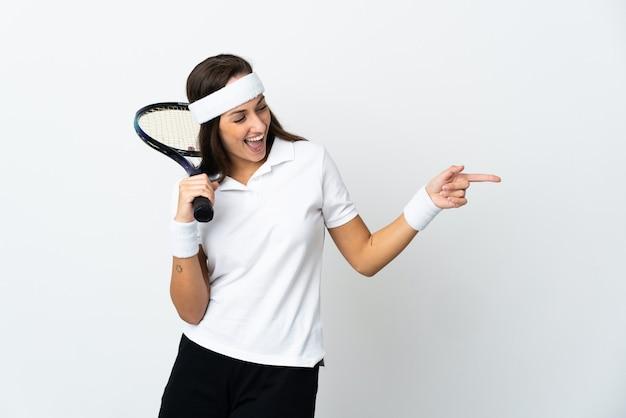 Молодая женщина-теннисистка над изолированной белой стеной, указывая пальцем в сторону и представляя продукт