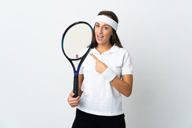 Молодая женщина-теннисистка над изолированной белой стеной, указывая в сторону, чтобы представить продукт